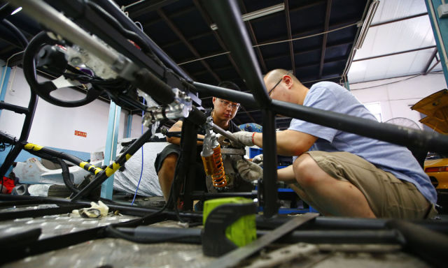 Wang and Li work on a replica of T-Rex motorcycle at a garage on the outskirts of Beijing