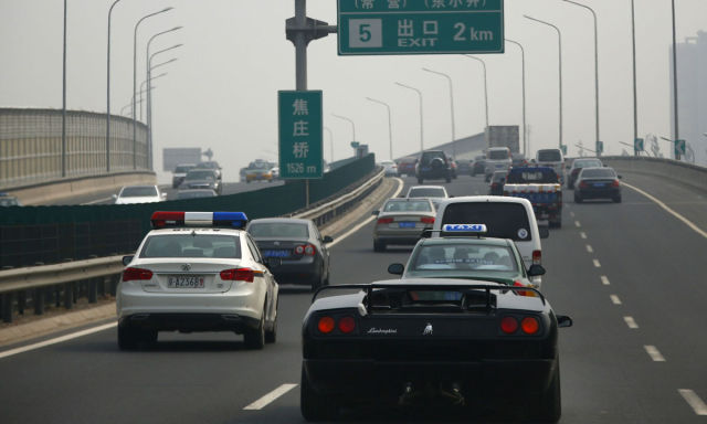 Wang Yu drives a handmade replica of Lamborghini Diablo next to a police car on a highway during a test drive in Beijing